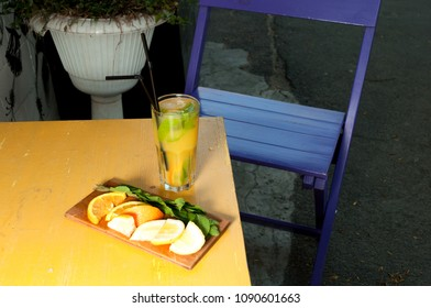 bright glass with lemonade summer cocktail with lemon, mint, orange with chopped slices on a yellow wooden table background