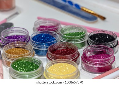 Bright glitter for nail decoration. Design on long nails from multicolored sequin closeup.Nail art.