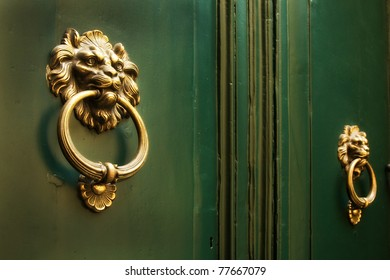 Bright gold lion doorknockers on a pair of old green doors