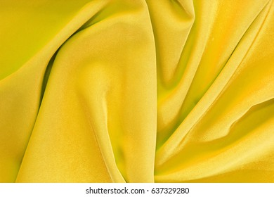 Bright golden fabric twisted texture with soft folds - perfect for background or your design