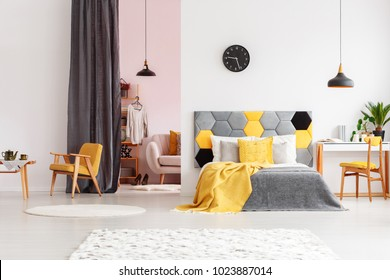 Bright, gray and yellow bedroom interior with pink dressing room behind a gray curtain
