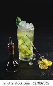 Bright green alcohol cocktail with cucumber garnish with honey and angostura on black background