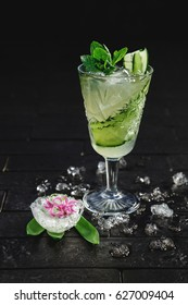 Bright green alcohol cocktail with cucumber garnish with ice and mint on black background