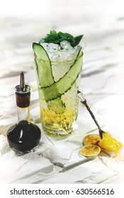 Bright green alcohol cocktail with cucumber garnish with honey and angostura on white background