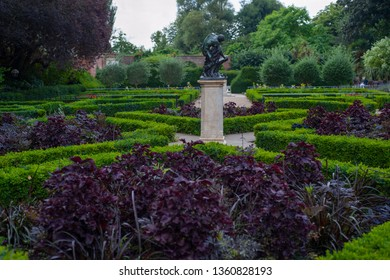 Bright green bushes and dark purple plants. The labyrinth from flower beds with a statue of a man in the center in the park.