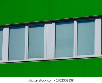 bright green color metal exterior siding of office building with white plastic strip windows. light gray window blind or shade. modern architecture concept. textures and patterns.