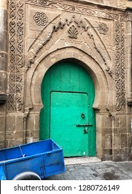 A bright green door contrasts with the blue hand cart and the ancient stone walls of the buildings in the souk of Essaouira, Morocco.