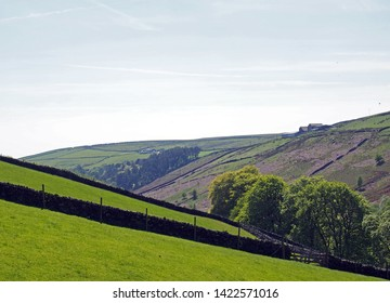 bright green grass meadows meadows with stone walls on the sides of a valley near crimsworth dean and above hardcastle crags in calderdale with forest trees and farmland in the distance