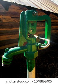 Bright green hose bib or spigot for water access on the park grounds.