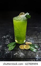 Bright green lemonade cocktail garnished with lemon and mint on black background