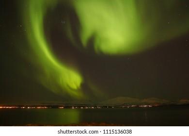 A bright green northern light on a dark Norwegian sky