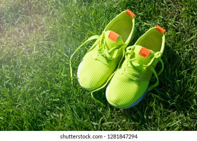 Bright green sneakers on grass background