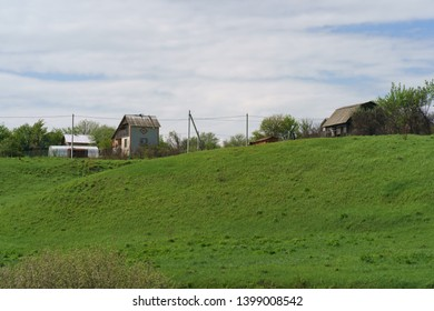Bright green spring countryside landscape of Russia. Houses on the Russian dacha on the hill.
