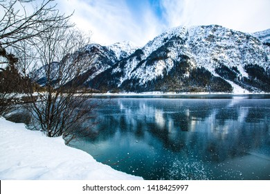 Bright green waters of winter lake and mountains, reflected in the water, Bayern, Germany.