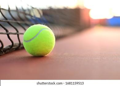 Bright greenish yellow tennis ball on clay court.