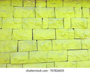 Bright greenish yellow vintage antique brick wall