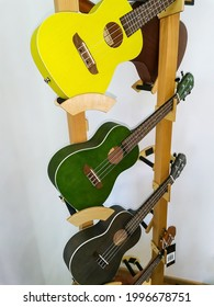 Bright guitars ukulele on a rack. Musical instruments in the store