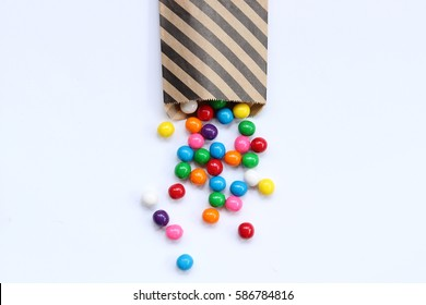 Bright gumballs spill out of a black striped treat bag onto white empty space for copy.