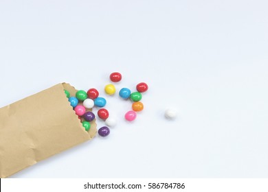 Bright gumballs spill out of a plain brown treat bag onto white empty space for copy.