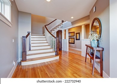 Bright hallway with wooden staircase. Staircase with white railings and brown trim