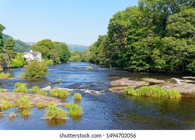 A bright, hazyy, summer day looking down the fast flowing, tree lined River Dee in Llangollen, Wales