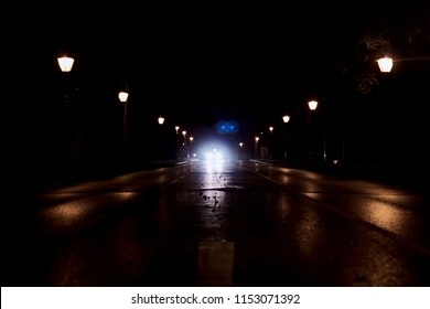 Bright headlights on road reflecting from the asphalt at night