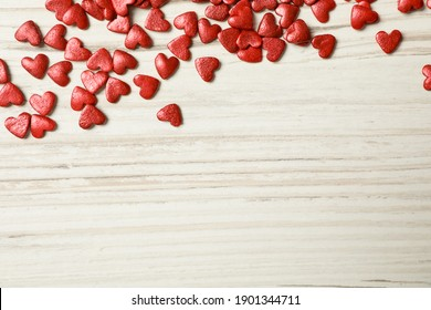 Bright heart shaped sprinkles on white wooden table, flat lay. Space for text