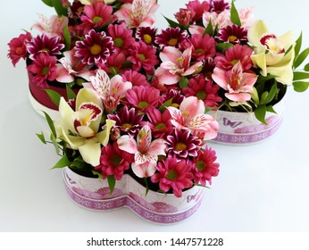 bright heart-shaped boxes with flowers in red on a white table close-up with a blurred background. green Orchid, pink Alstroemeria, variegated chrysanthemum, pink chrysanthemum.