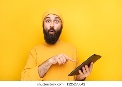 Bright hipster in hat and sweater pointing at tablet in hands looking amazed on yellow.