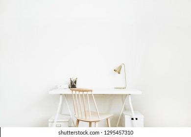 Bright home office desk workspace. Nordic modern minimal interior design concept. Desktop table and wooden chair in white room. Scandinavian style.