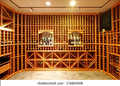 Bright home wine cellar with wooden storage units and arch with bottles.