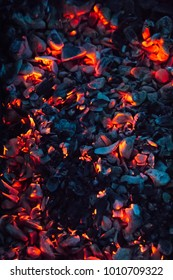 Bright hot coals and burning woods in bbq grill pit. Glowing and flaming charcoal, barbecue, red fire and ash. Weekend recreation background. Close-up, top view.
