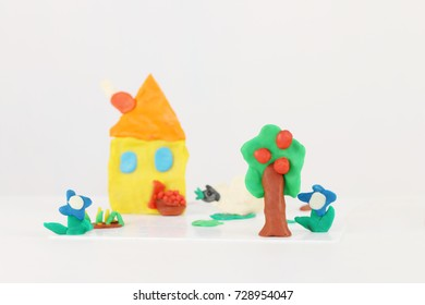 Bright house, sheep, flowers, tree from plasticine on white table