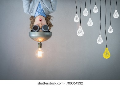Bright idea! Child playing with light bulb. Kid with toy virtual reality headset. Success, idea and innovation technology concept. Back to school