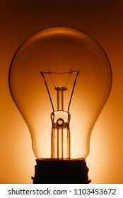 A Bright Idea - Standard electric incandescent glass light bulbs black silhouette with the filament between two vertical supply wires in orange backlit