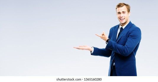 Bright image of businessman showing something, over grey background. Copyspace area for slogan or advertising text message. Success in business, job and education concept studio shot.