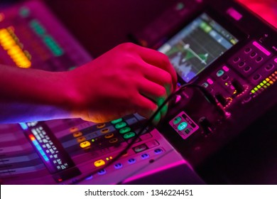 Bright image of hands of sound engineer working with concert sound equiplment- audio mixing music console with backlit buttons. Sound,music equipment and technology concept