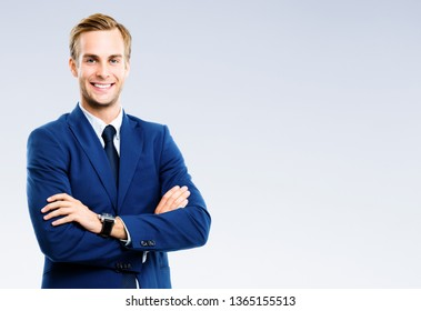 Bright image of happy smiling young businessman, over grey background. Business success concept.