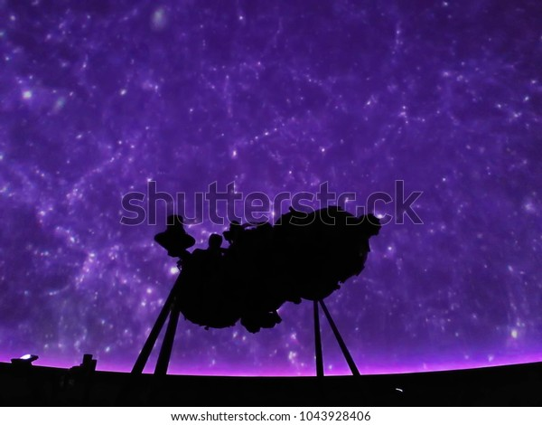 Bright image of many star on the sky projected on purple light screen with shadow of old analog projector at planetarium in Thailand.
