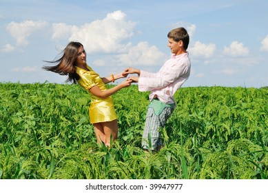 Bright image with young couple resting on green field