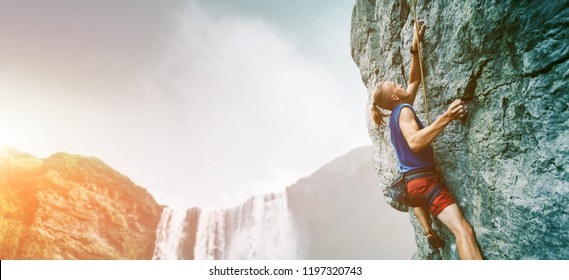 bright image of young man rock climber with long hair wearing in bright red shorts and blue t-shirt climbing the challenging route on the cliff. rock climber climbing on a limestone wall on the
