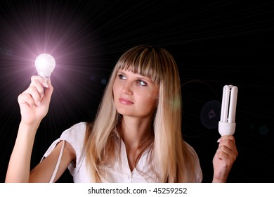 bright incandescent bulb in young woman hands on black background