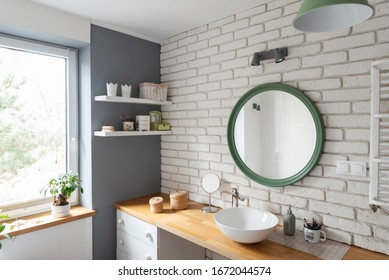 Bright interior of bathroom with window and white brick wall. Stylish interior with round mirror and wooden furniture and counter. Scandinavian style.