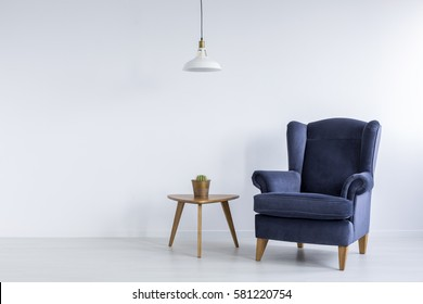 Bright interior with blue armchair, ceiling lamp and side table
