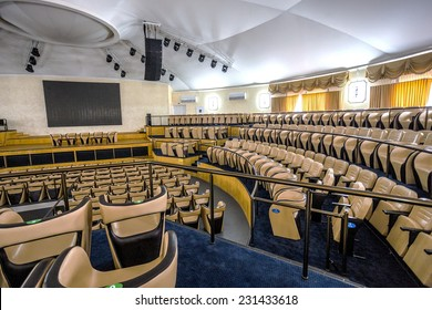 Bright interior of a modern concert hall with a stage and rows of comfortable leather chairs, a stage and acoustic amplification system under natural light, prepared for presentation