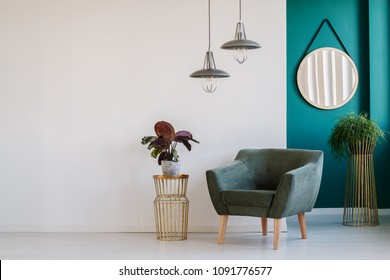 Bright interior in white and green with armchair, table with plant, lamps and mirror