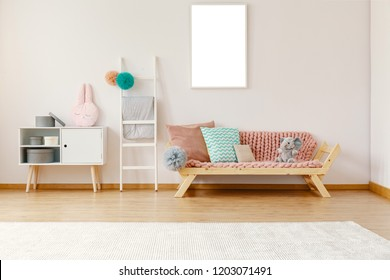 Bright kid room interior with wooden couch with powder pink coverlet, cushions and elephant, white carpet on the floor, ladder with pompoms and mockup poster on the wall in the real photo
