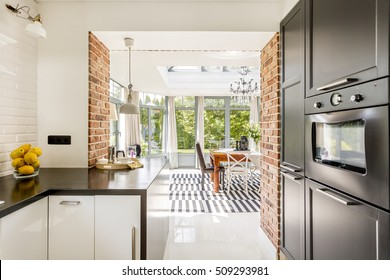 Bright kitchen area with modern amenities, close brick walls with the view of minimalistic dining room surrounded by windows