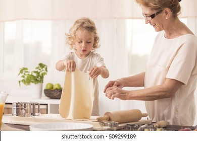 Bright kitchen interior with child making the cake with it's smiled grandmother