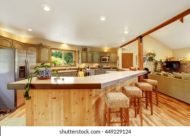 Bright kitchen room interior with large wooden bar and stainless steel fridge. View of the living room.
